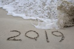 2019 holiday concept. The number 2019 written in the sand by the ocean with wave royalty free illustration