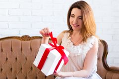 Holiday concept - portrait of beautiful woman opening gift box. Holiday concept - portrait of young beautiful woman opening gift box Stock Photo