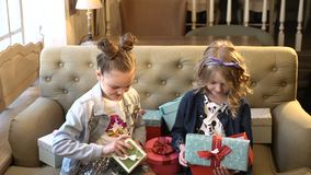 Holiday concept. Two pretty little girls sit together holding bright boxes with presents trying to open them. Suitable. For every feast, event or holiday. hd stock video