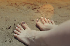 Holiday concept. Woman feet close-up relaxing on beach, enjoying sun and splendid view Royalty Free Stock Image