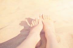 Holiday concept. Woman feet close-up relaxing on beach, enjoying sun and splendid view. Sandy feet on the beach. Sun, sun haze, gl Royalty Free Stock Photography