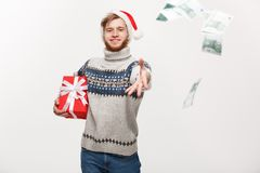 Holiday Concept - Young beard man holding christmas gift and throwing money to camera. stock photo
