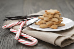 Holiday cookies and candy canes on wood table Royalty Free Stock Images