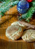Holiday cinnamon snicker-doodle cookies. Holiday cookies with cinnamon sugar topping and cinnamon sticks with a fir tree and ornament background Stock Images