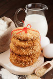Holiday cookies with red ribbon, flour, milk jug and eggs on kit Royalty Free Stock Photo