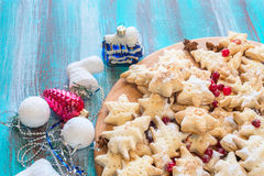 Holiday cookies surrounded by Christmas-tree decorations. Holiday cookies with cranberries and spices lie on the turquoise wooden table  surrounded by Christmas Stock Images