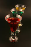 Holiday Cordials. Three cordials in a skewed line with red, green and gold liquid Royalty Free Stock Image