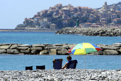 Holiday in corse. Couple is sitting under an umbrella on the beach, in the background is a village Stock Photography