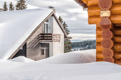 Holiday cottages in the mountains. In the background alpine landscape and forests Stock Photo