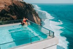 Holiday Couple relaxing in luxury with tropical water villa resort luxurious swimming pool with ocean view Bali , Indonesia