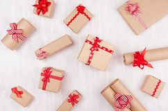 Holiday craft paper gifts with red bows on soft white wood board as celebration random pattern. Holiday craft paper gifts with red bows on soft white wood board royalty free stock image