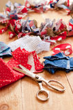 Holiday crafting. Strips of fabric have been cut by a pinking shears to create a patriotic fabric wreath with burlap to celebrate the 4th of July Royalty Free Stock Image