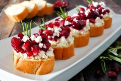 Holiday crostini appetizers with cranberries, pomegranates and feta, close up table scene. Holiday crostini appetizers with cranberries, pomegranates and feta stock photos
