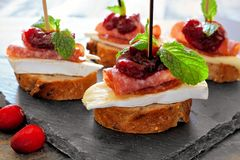 Holiday crostini with cranberry sauce, close up on slate Stock Photos