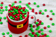 Holiday cup spilling of Candy onto old wood Royalty Free Stock Photos
