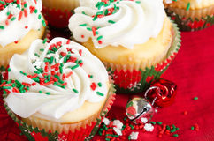 Holiday cupcakes with vanilla frosting, red and green sprinkles Royalty Free Stock Images