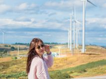 Holiday dating and couple activity with asian woman with cloth a. Nd sunglasses travel pose and see to her boyfriend take photo with wind turbine background Royalty Free Stock Image