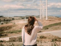 Holiday dating and couple activity with backside of asian woman. Travel stand with sleek pose and see to sky for her boyfriend take photo with wind turbine Royalty Free Stock Images