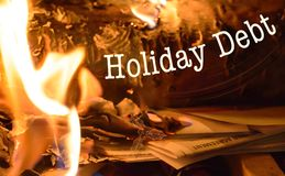 Holiday debt and stress. Fire burning pile of bills and Christmas holiday expenses conceptual image with copy space and cardholder credit card agreement burning Stock Photo