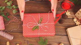 Woman`s hands tying christmas holiday handmade present in craft paper with twine ribbon. Holiday decor concept. Woman`s hands tying christmas holiday handmade stock video