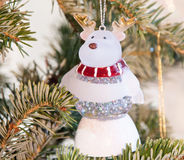 Holiday decor deer on Christmas tree. Horizontal image has on the left side a part of the christmas tree and on the middle is decoration that hang from it is Stock Photography