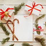 Holiday Decor Notebook for Message with gift, present box and candy cane. Christmas Background. Top view Royalty Free Stock Photography