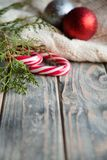 Holiday decor wooden background candy cane juniper. Holiday decoration on wooden background. stripy candy cane juniper twig and balls on knitted blanket on royalty free stock photography