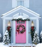 Holiday decorated entrance. Snowy home entrance decorated with holiday wreath and evergreens Stock Images