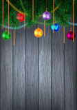 Holiday decorated evergreen on wood. Christmas or New Year colorful greeting card with evergreen pine branch and baubles with tinsel. Decorated wood background Royalty Free Stock Photography