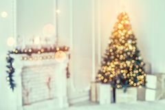 Holiday decorated room with Christmas tree and decoration, background with blurred, sparking, glowing light. Happy New Year and Xmas theme, toning stock photo