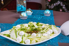 Holiday-decorated table, Christmas toys and zucchini salad. Stock Photo