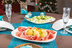 Holiday-decorated table, Christmas tree, ham and melone, and sal Royalty Free Stock Image