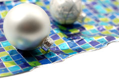 Holiday Decoration. Ornaments resting over wrinkled used torn wrapping paper on white background Stock Images