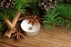 Holiday decoration with candle,fir and cinnamon on wooden backgr Stock Image