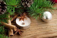 Holiday decoration with candle,fir and cinnamon on wooden backgr Royalty Free Stock Image
