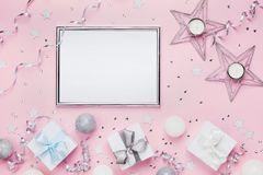 Holiday decoration, frame and gift boxes on stylish pink table top view. Fashion christmas background. Flat lay. Party mockup. royalty free stock photos