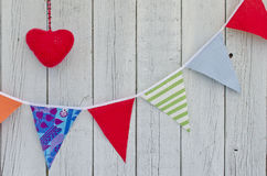 Holiday decoration. Red heart and multicolored flags Stock Photography