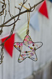 Holiday decoration. Star on a branch and multicolored flags Royalty Free Stock Photography