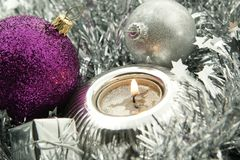 Christmas Decoration. Holiday decoration with tinsel, candle and bauble in silver and pink Royalty Free Stock Images