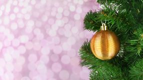 Holiday decoration toy ball on a Christmas tree in golden color. On a pink background with a bokeh Royalty Free Stock Image
