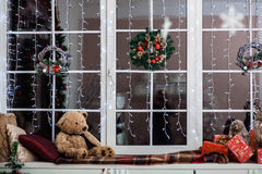 Holiday decoration on the windowsill covered with woolen plaid. Christmas wreath, lights and toys Royalty Free Stock Photography