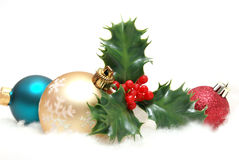 Holiday Decorations. A holiday scene of holly and golden baubles on some artifical snow royalty free stock images