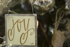Holiday decorations, Christmas ornament Joy. Christmas home decoration, close up of an ornament sign Joy hanging on the tree royalty free stock image