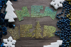 Holiday decorations closeup on wooden background with holographic inscription New Year. Stock Photos