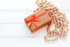 Holiday decorations, gift box and beads on white wood background Stock Image