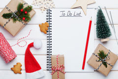 Holiday decorations, gift, present box, miniature fir tree and notebook with christmato do list on white wooden table from above. Royalty Free Stock Photos