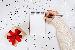 Holiday decorations and notebook with wish list. On white rustic table, flat lay style. Planning concept Royalty Free Stock Images