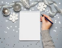 Holiday decorations and notebook with wish list on white rustic table, flat lay style. Planning concept. Holiday decorations and notebook with wish list on Royalty Free Stock Image