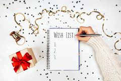 Holiday decorations and notebook with wish list. On white rustic table, flat lay style. Planning concept Royalty Free Stock Photos