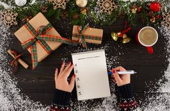 Close up of hands holding empty wishlist on wooden table with Christmas decoration. stock photos